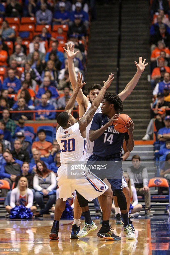 Guard Lindsey Drew of the Nevada Wolf Pack finds the defense of guard Paris Austin and forward Zach Haney of the Boise State Broncos tough during...