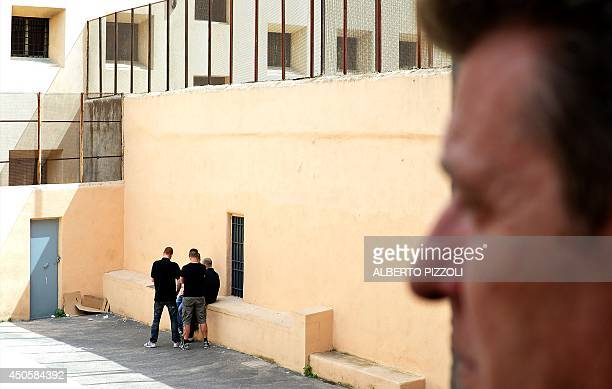 A guard looks on as prisoners chat in the courtyard of Regina Coeli prison in Rome on May 30 2014 Crouched on bunk beds in the narrow cells of the...