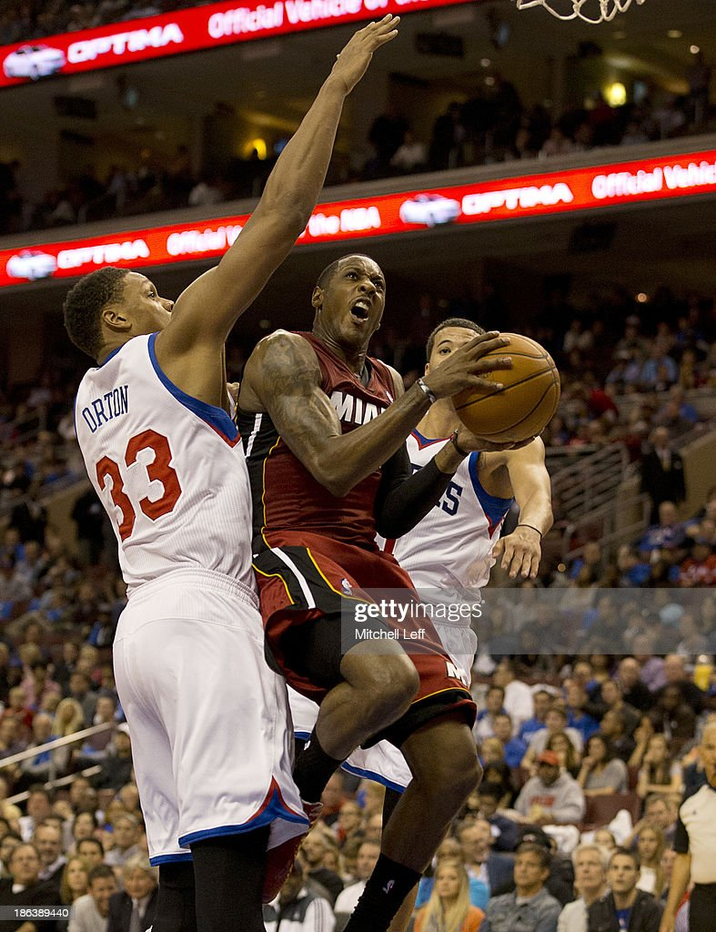 Guard <a gi-track='captionPersonalityLinkClicked' href=/galleries/search?phrase=Mario+Chalmers&family=editorial&specificpeople=802115 ng-click='$event.stopPropagation()'>Mario Chalmers</a> #15 of the Miami Heat drives to the basket with center <a gi-track='captionPersonalityLinkClicked' href=/galleries/search?phrase=Daniel+Orton&family=editorial&specificpeople=5817674 ng-click='$event.stopPropagation()'>Daniel Orton</a> #33 of the Philadelphia 76ers on October 30, 2013 at the Wells Fargo Center in Philadelphia, Pennsylvania.