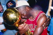 Guard Michael Jordan of the Chicago Bulls sits nexts to his wife Juanita and his dad James while hugging the NBA Championship Trophy after the Bulls...