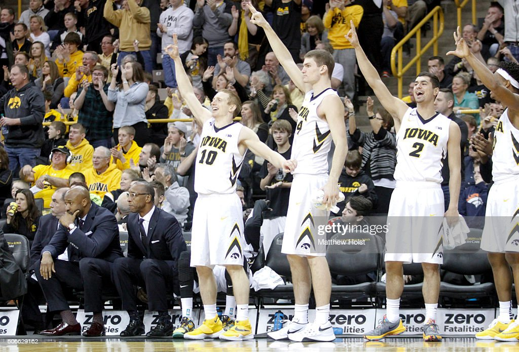 Guard Mike Gesell center Adam Woodbury and guard Andrew Feming of the Iowa Hawkeyes celebrate on the bench after a basket against the Purdue...