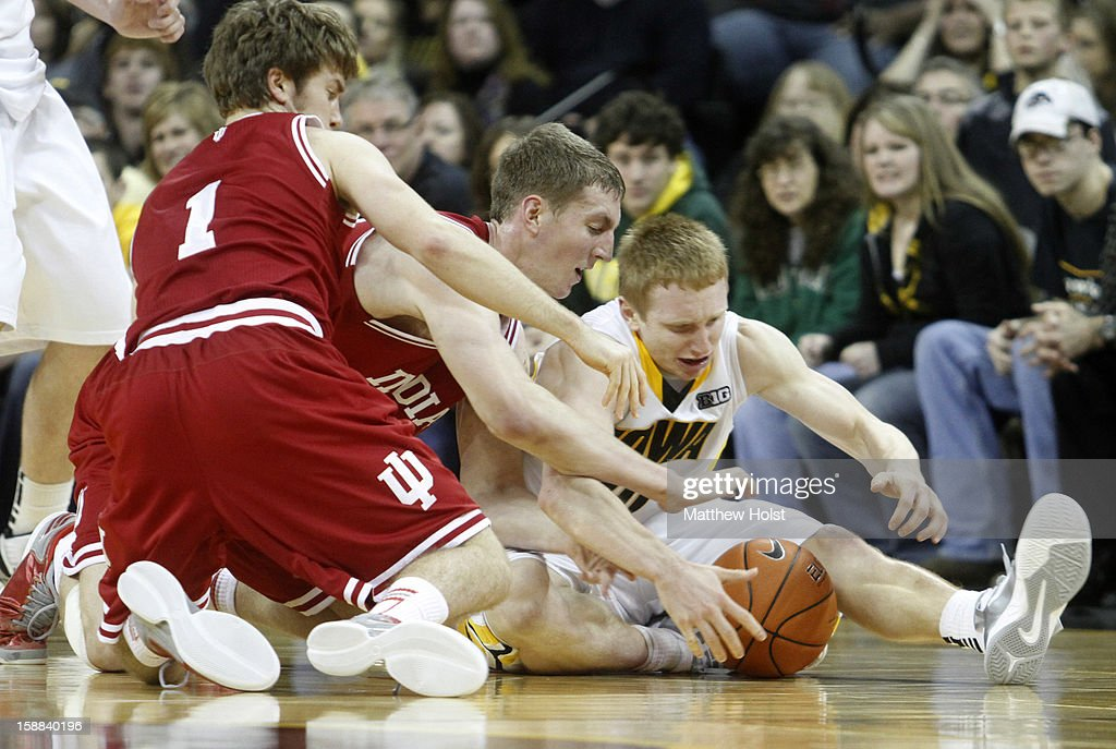 Guard Mike Gesell #10 of the Iowa Hawkeyes battles for a loose ball during the second half with guard Jordan Hulls #1 and forward <a gi-track='captionPersonalityLinkClicked' href=/galleries/search?phrase=Cody+Zeller&family=editorial&specificpeople=7621233 ng-click='$event.stopPropagation()'>Cody Zeller</a> #40 of the Indiana Hoosiers on December 31, 2012 at Carver-Hawkeye Arena in Iowa City, Iowa. Indiana won 69-65.