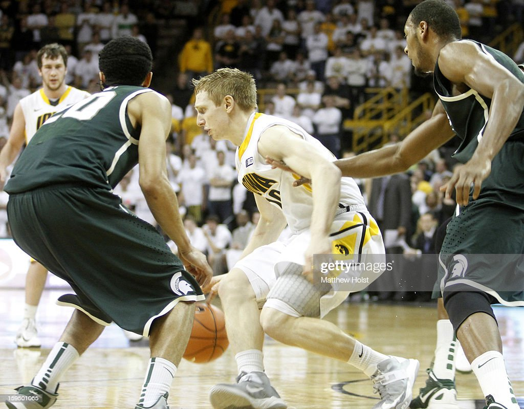 Guard Mike Gesell #10 of the Iowa Hawkeyes brings the ball down the court during the second half between guard Travis Trice #20 and center Adreian Payne #5 of the Michigan State Spartans on January 10, 2013 at Carver-Hawkeye Arena in Iowa City, Iowa. Michigan State won 62-59.