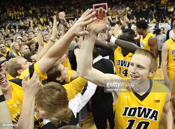 Guard Mike Gesell of the Iowa Hawkeyes celebrates with fans who stormed the court after defeating the Michigan State Spartans on December 29 2015 at...