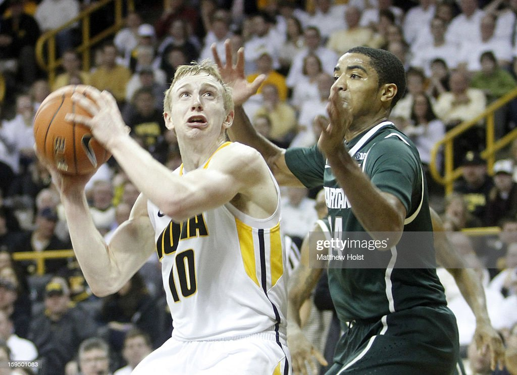 Guard Mike Gesell #10 of the Iowa Hawkeyes drives down the court during the second half against guard Gary Harris #14 the Michigan State Spartans on January 10, 2013 at Carver-Hawkeye Arena in Iowa City, Iowa. Michigan State won 62-59.
