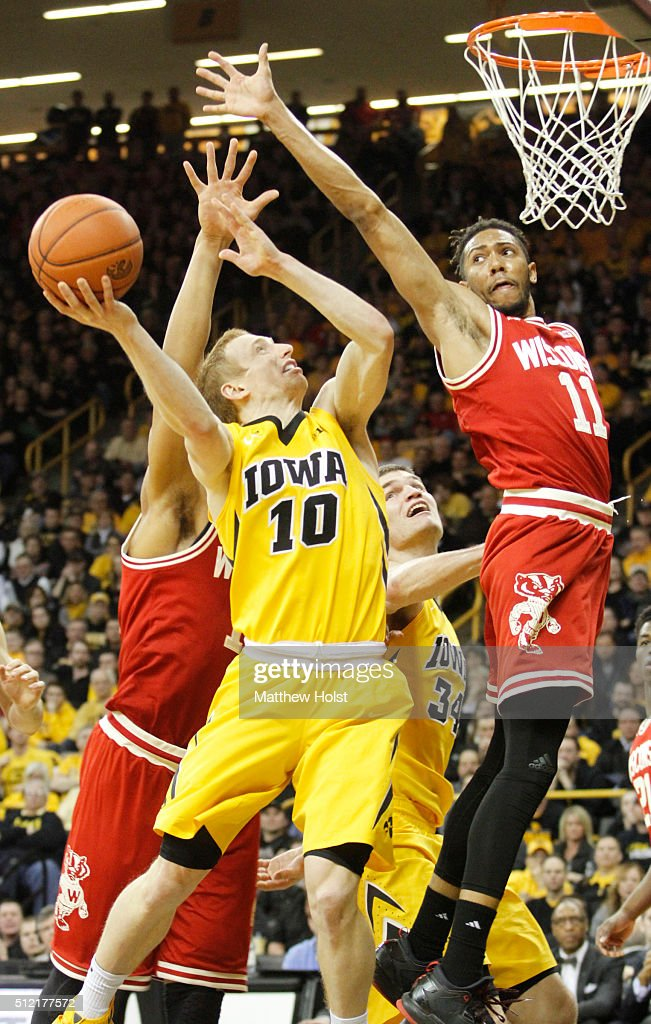 Guard Mike Gesell of the Iowa Hawkeyes goes to the basket between forward Charlie Thomas and guard Jordan Hill of the Wisconsin Badgers in the second...