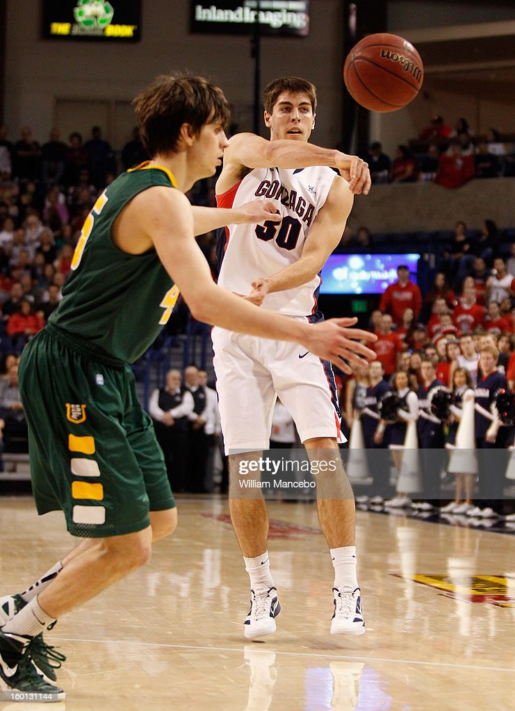 Guard Mike Hart #30 of the Gonzaga Bulldogs passes the ball with guard Cody Doolin #45 of the San Francisco Dons seen in the foreground during the game at McCarthey Athletic Center on January 26, 2013 in Spokane, Washington.