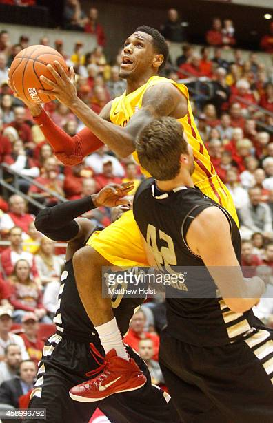 Guard Monte Morris of the Iowa State Cyclones drives to the basket between center Corey Petros and guard Kahlil Felder of the Oakland Golden...