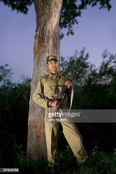 A guard named Bourn Gogi stands beneath a tree that was clawed by a wild tiger several feet above his head earlier in the day Nearly 90 tigers live...