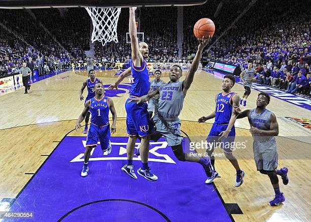 Guard Nigel Johnson of the Kansas State Wildcats drives to the basket past forward Perry Ellis of the Kansas Jayhawks during the first half on...