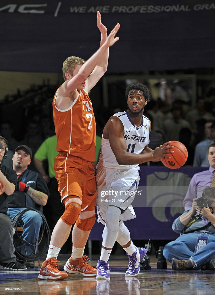 Guard Nino Williams #11 of the Kansas State Wildcats looks to make a pass against forward Connor Lammert #21 of the Texas Longhorns during the first half on January 30, 2013 at Bramlage Coliseum in Manhattan, Kansas.