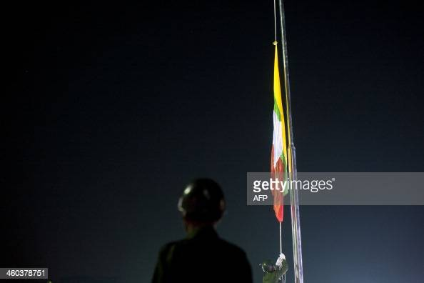 A guard of honor raises the national flag of Myanmar during a flagraising ceremony to mark Myanmar's 66th Independence Day at the People's Square...