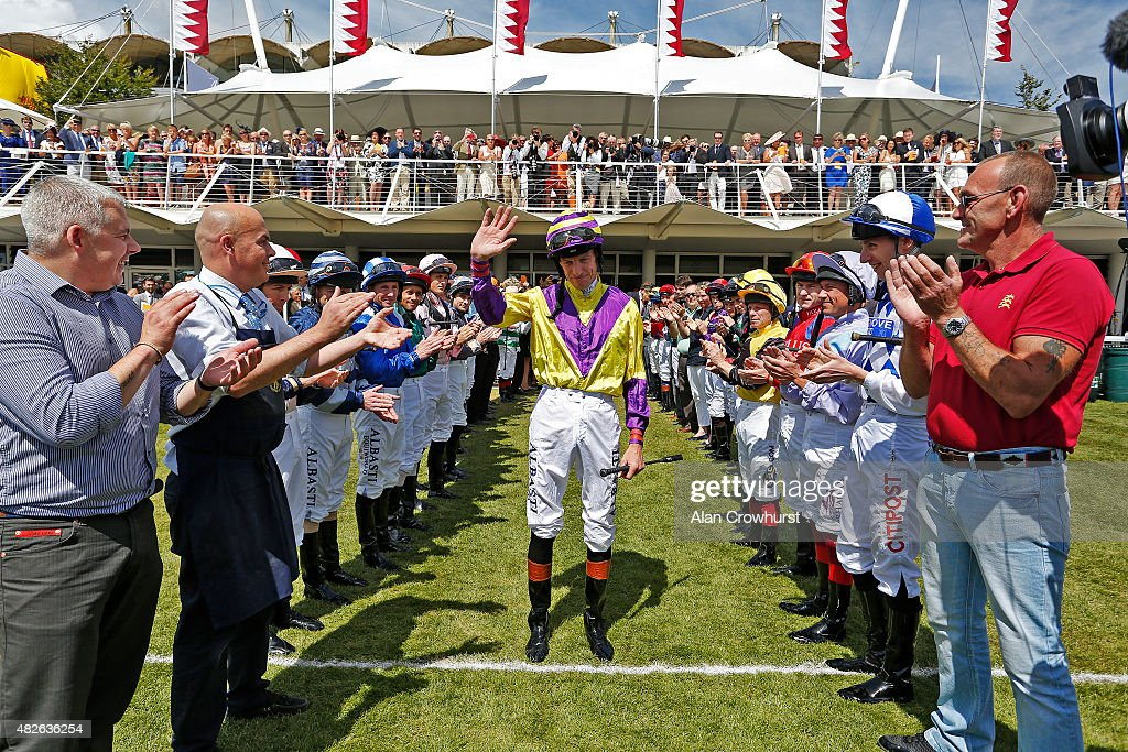 A guard of honour is formed for jockey Richard Hughes as he retires from race riding at the end of the day at Goodwood racecourse on August 01, 2015 in Chichester, England.