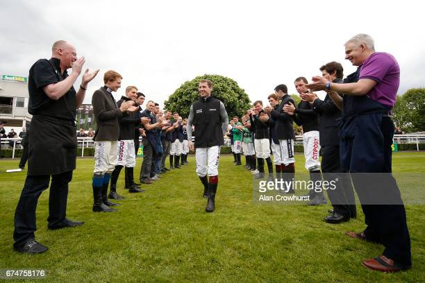A guard of honour is formed for Richard Johnson who is crowned Champion Jockey at Sandown Park on April 29 2017 in Esher England