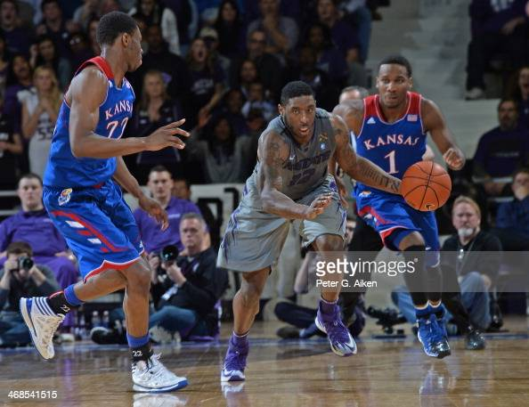 Guard Omari Lawrence of the Kansas State Wildcats drives up court against defenders Wayne Selden Jr #1 and Andrew Wiggins of the Kansas Jayhawks...