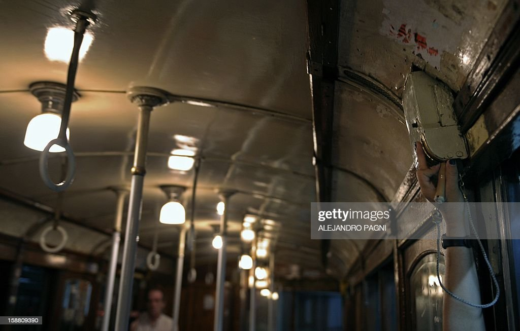 A guard opens the doors of one of the historic wagons La Brugeoise of subway Line A, which is expected to be close soon following a decision by city mayor Mauricio Macri to replace the fleet with Chinese-made wagons, in Buenos Aires, on December 29, 2012. Line A was the first subway line to work in the southern hemisphere and its trains are among the ten oldest still working daily. The La Brugeoise wagons were constructed between 1912 and 1919 by La Brugeoise et Nicaise et Delcuve in Belgium. AFP PHOTO / ALEJANDRO PAGNI