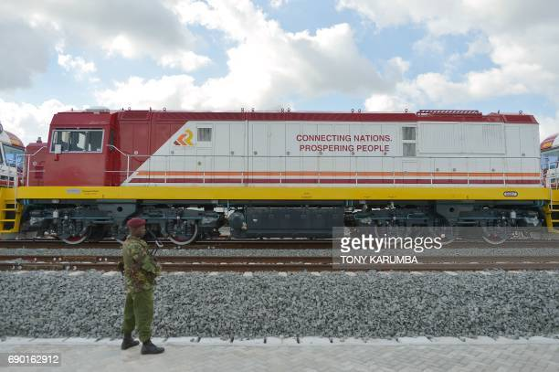 A guard passes a locomotive train car at the container terminal of the port of the coastal town of Mombasa on May 30 2017 More than a century after a...