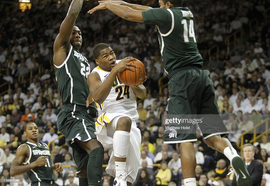 Guard Pat Ingram #24 of the Iowa Hawkeyes drives to the basket during the second half against guards Gary Harris #14 and Branden Dawson #22 of the Michigan State Spartans on January 10, 2013 at Carver-Hawkeye Arena in Iowa City, Iowa. Michigan State won 62-59.