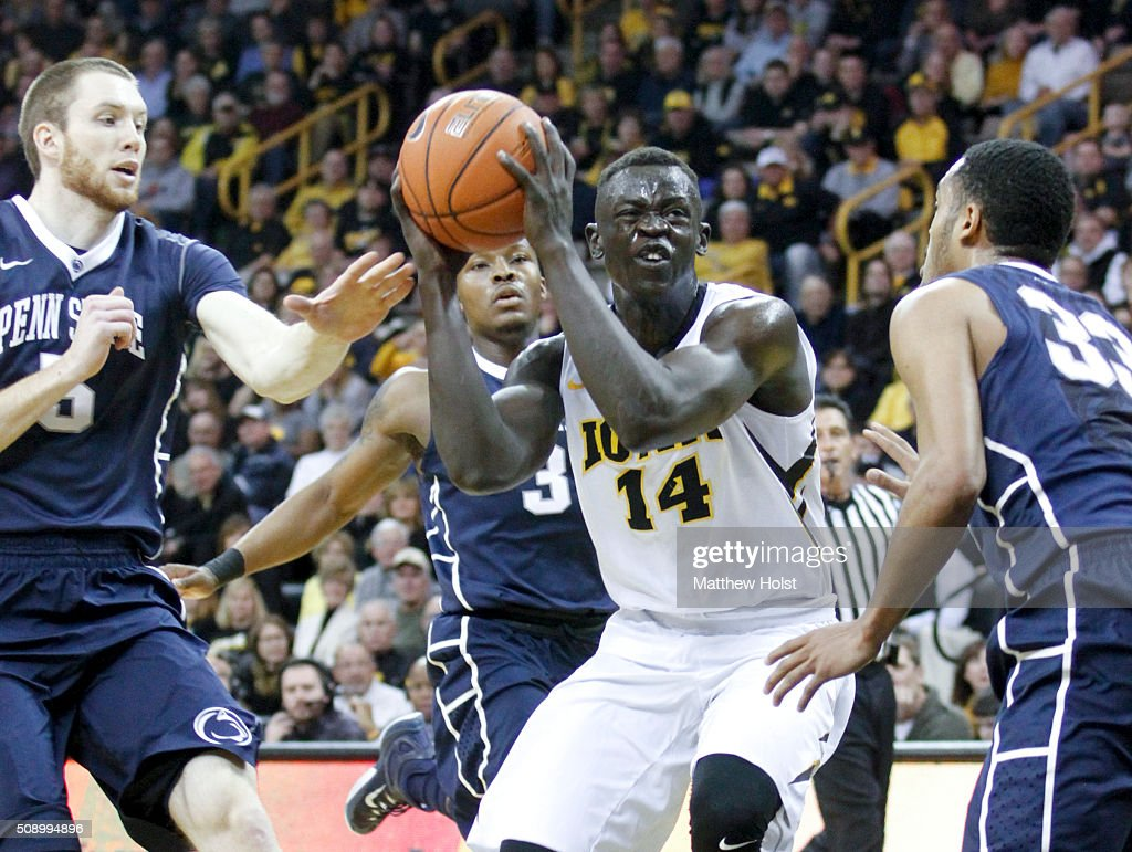 Guard Peter Jok of the Iowa Hawkeyes drives between guard Shep Garner and forward Donovan Jack of the Penn State Nittany Lions in the first half on...