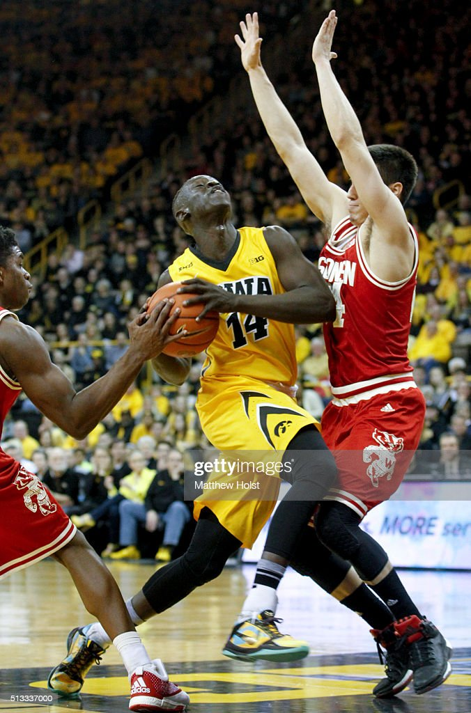 Guard Peter Jok of the Iowa Hawkeyes goes to the basket between guards Jordan Hill Bronson Koenig of the Wisconsin Badgers in the first half on...