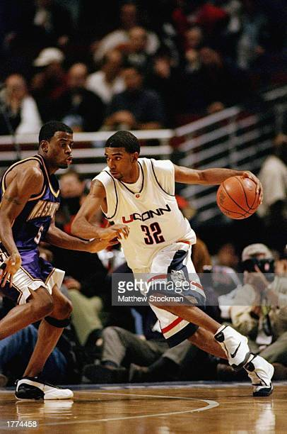 Guard Richard Hamilton of the University of Connecticut Huskies drives against guard Deon Luton of the Washington Huskies during the Great Eight...