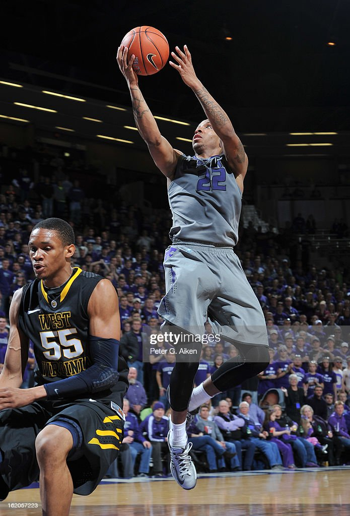 Guard Rodney McGruder #22 of the Kansas State Wildcats drives in for a basket over forward Keaton Miles #55 of the West Virginia Mountaineers during the second half on February 18, 2013 at Bramlage Coliseum in Manhattan, Kansas. Kansas State defeated West Virginia 71-61.