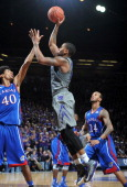Guard Rodney McGruder of the Kansas State Wildcats puts up a shot over forward Kevin Young of the Kansas Jayhawks during the second half on January...