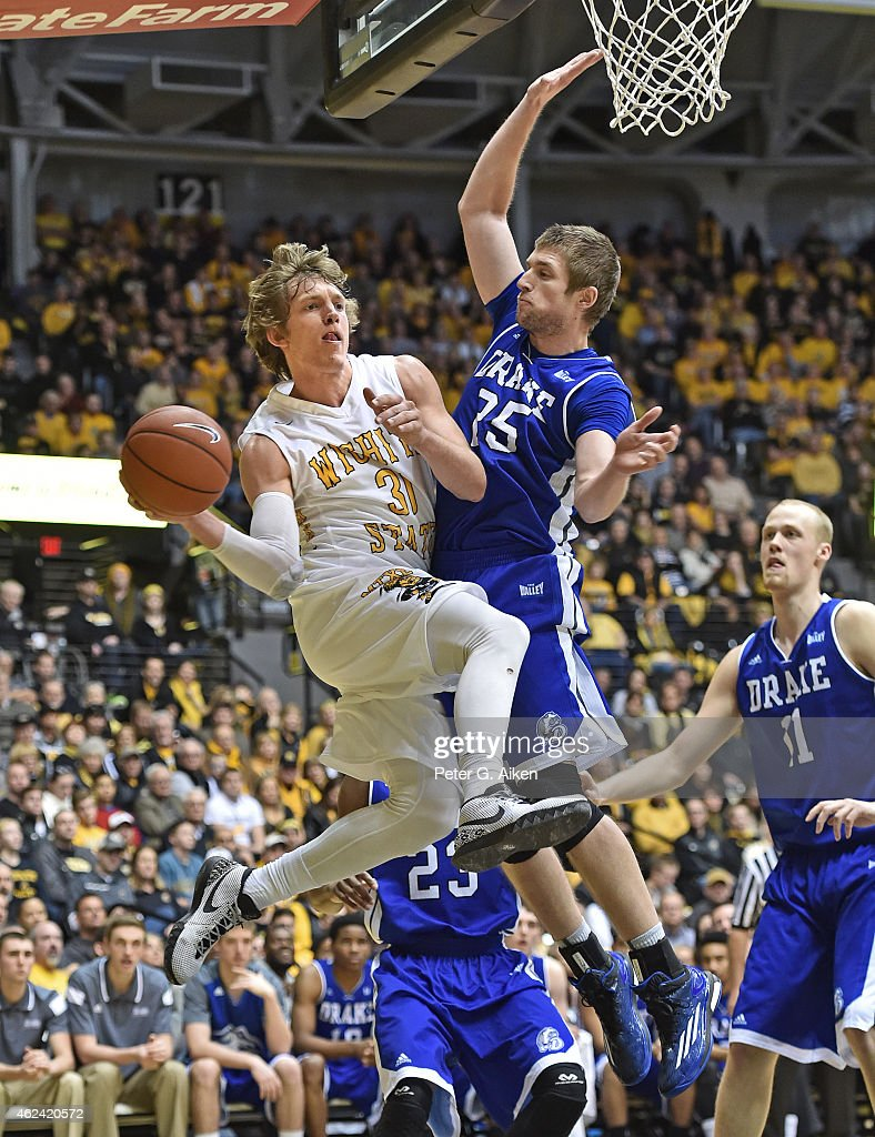 Guard <a gi-track='captionPersonalityLinkClicked' href=/galleries/search?phrase=Ron+Baker+-+Joueur+de+basketball&family=editorial&specificpeople=13909614 ng-click='$event.stopPropagation()'>Ron Baker</a> #31 of the Wichita State Shockers drives to the basket against guard Chris Caird #25 of the Drake Bulldogs during the first half on January 25, 2015 at Charles Koch Arena in Wichita, Kansas.