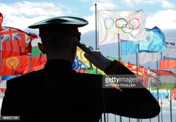 A guard salutes during a flag raising ceremony in the athletes olympic village prior to the start of the 2014 Sochi Winter Olympics on February 1...
