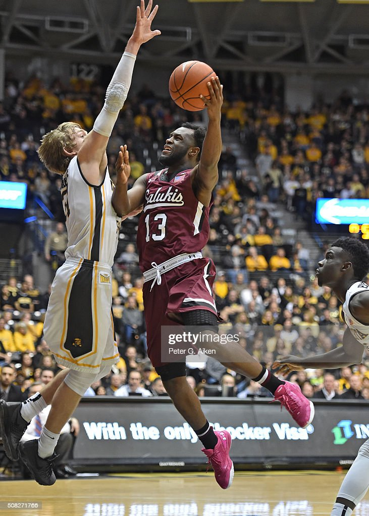 Guard Sean Lloyd #13 of the Southern Illinois Salukis drives to the basket against guard <a gi-track='captionPersonalityLinkClicked' href=/galleries/search?phrase=Ron+Baker+-+Jogador+de+basquetebol&family=editorial&specificpeople=13909614 ng-click='$event.stopPropagation()'>Ron Baker</a> #31 of the Wichita State Shockers during the second half on February 3, 2016 at Charles Koch Arena in Wichita, Kansas. Wichita State defeated Southern Illinois 76-55.