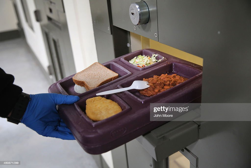 A guard serves lunch to an immigrant detainee in his 'segregation cell' during lunchtime at the Adelanto Detention Facility on November 15 2013 in...