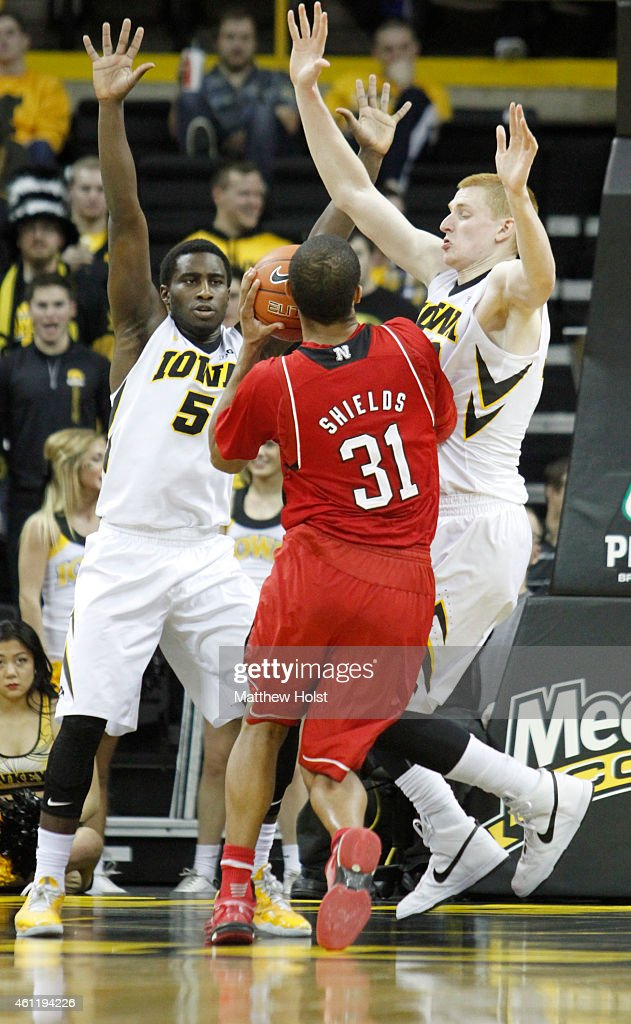 Guard Shavon Shields #31 of the Nebraska Cornhuskers goes to the basket against guard Anthony Clemmons #5 and forward <a gi-track='captionPersonalityLinkClicked' href=/galleries/search?phrase=Aaron+White+-+Basketball+Player&family=editorial&specificpeople=14619648 ng-click='$event.stopPropagation()'>Aaron White</a> #30 of the Iowa Hawkeyes, in the second half on January 5, 2015 at Carver-Hawkeye Arena, in Iowa City, Iowa.