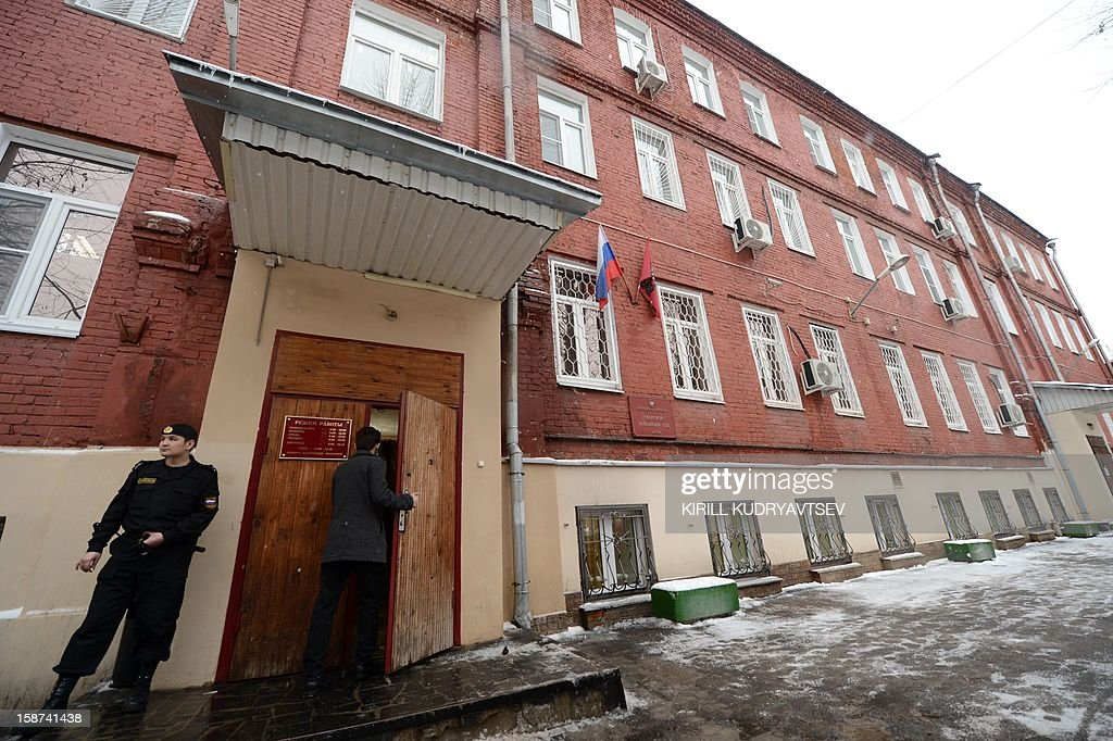 A guard stands at an entrance to the Tverskoy district court in Moscow, on December 27, 2012, ahead of the start of preliminary hearing into the case of Russian lawyer Sergei Magnitsky. Russia opened today a fraud trial against Sergei Magnitsky, whose prison death in 2009 led to the biggest US-Russia row in years, despite protests by the defence it was illegal to try a dead man. 'The preliminary hearing into Magnitsky's case has been moved to January 28 due to the absence of the lawyers from the defence,' the press service of the court told AFP. AFP PHOTO / KIRILL KUDRYAVTSEV