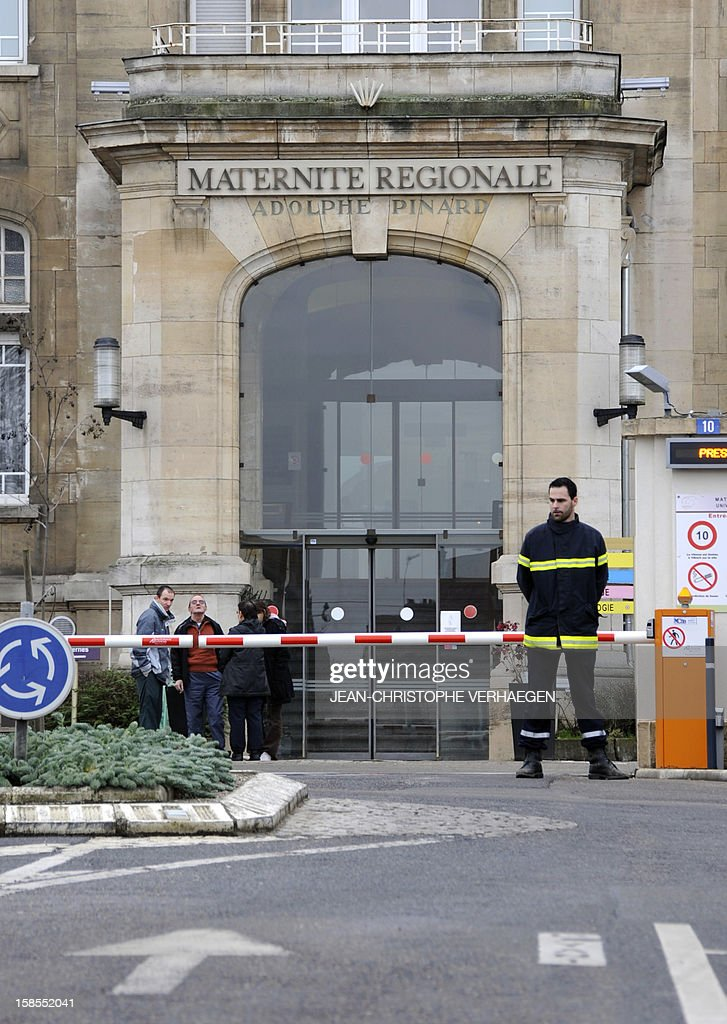 A guard stands at the entrance of the regional maternity in Nancy, eastern France, on December 19, 2012, a day after a young woman kidnapped a new born baby. The woman introduced herself as a medical assistant and took the baby as the mother was sleeping. VERHAEGEN