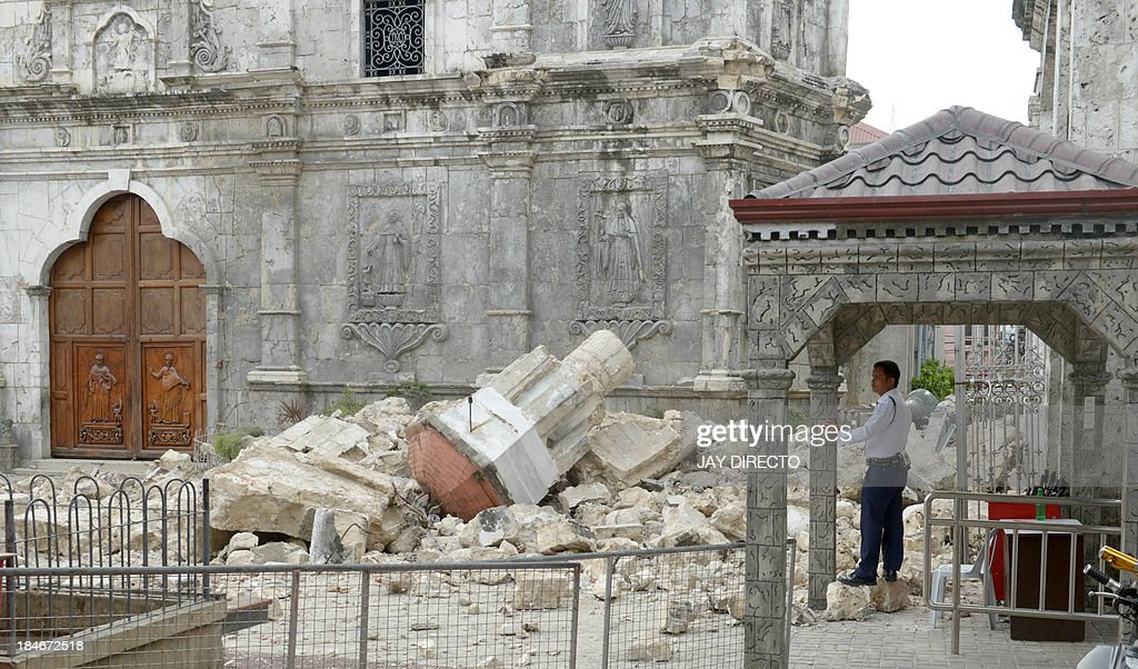 A guard stands beside the ruins of Basilica Minore del Santo Nino bell tower following a 7.1-magnitude quake in Cebu on October 15, 2013. A powerful earthquake killed at least 73 people on October 15 as it tore down modern buildings, destroyed historic churches and triggered terrified stampedes across popular tourist islands in the Philippines. AFP PHOTO / Jay DIRECTO