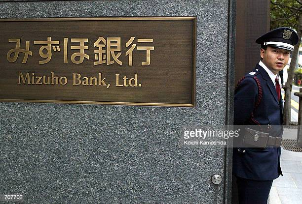 A guard stands in front of the Mizuho Bank headquarters April 16 2002 in Tokyo Mizuho Bank has fixed computer system glitches affecting its automatic...
