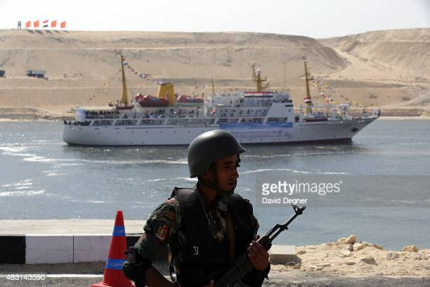 A guard stands in front Suez Canal as the Aida IV passes during the opening ceremony of the new Suez Canal expansion including a new 35km channel on...