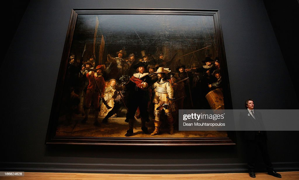 A guard stands next to The Nightwatch by Rembrandt four days after the Rijksmuseum Official Opening on April 17, 2013 in Amsterdam, Netherlands. The 10-year renovation of the Rijksmuseum is one of the most significant ever undertaken by a museum. The entire building has been renewed – the historic 19th-century building has been transformed and new public facilities have been created including a spectacular new entrance hall, a new Asian pavilion and renovated gardens. The museum features over 8,000 works of art and artefacts telling the story of 800 years of Dutch art and history, from the Middle Ages to the present day. The world-famous collection, including masterpieces by artists such as Frans Hals, Jan Steen, Johannes Vermeer and Rembrandt van Rijn, have been presented in chronological sequence for the first time, creating an awareness of time and a sense of beauty.