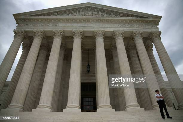 A guard stands on the steps of the Supreme Court Building August 20 2014 in Washington DC Today the high court blocked gay and lesbian couples from...