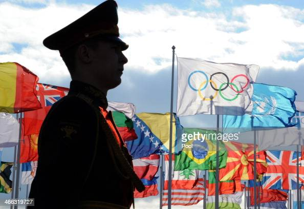 A guard stands to attention during a flag raising ceremony in the Athletes Olympic Village prior to the Sochi 2014 Winter Olympics at the Olympic...