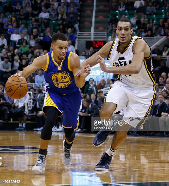 Guard Stephen Curry of the Golden State Warriors drives past Center Rudy Gobert of the Utah Jazz during the first half of an NBA game November 30...