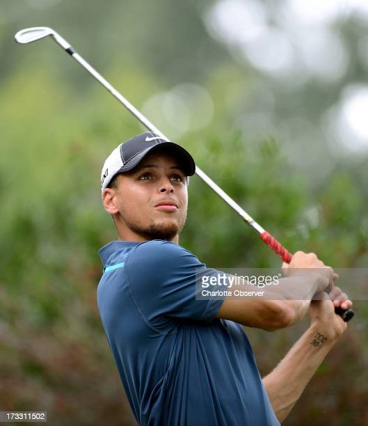 NBA guard Stephen Curry watches his drive from the ninth tee box during Fred Whitfield's 11th annual HoopTee Celebrity Golf Classic at The Golf Club...