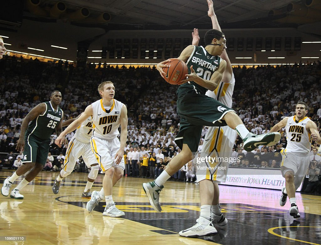 Guard Travis Trice #20 of the Michigan State Spartans drives to the basket during the second half against forward Zach McCabe #15 of the Iowa Hawkeyes on January 10, 2013 at Carver-Hawkeye Arena in Iowa City, Iowa. Michigan State won 62-59.