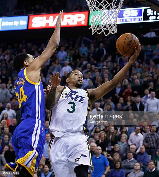 Guard Trey Burke of the Utah Jazz lays a shot over guard Shaun Livingston of the Golden State Warriors during the second half of an NBA game November...