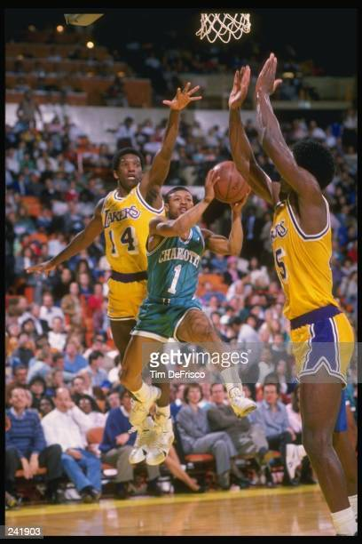 Guard Tyrone Bogues of the Charlotte Hornets goes up for two between guard David Rivers and forward A K Green of the Los Angeles Lakers during a game...