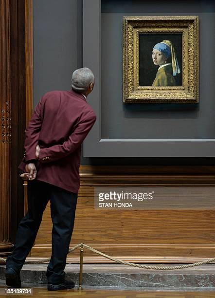 A guard views 'Girl with a Pearl Earring ' by Johannes Vermeer in the exhibition 'Vermeer Rembrandt and Hals Masterpieces of Dutch Painting from the...