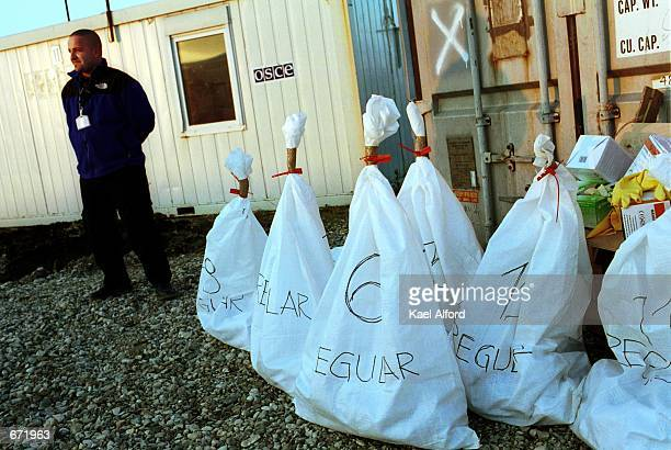 A guard watches over mailin ballots for Kosovo's general elections November 17 2001 near Pristina Kosovo Election officials have been scrutinizing...