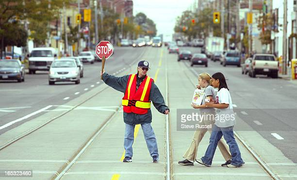 GUARD09/30/03Crossing guard Donna Harris helps children cross Lakeshore West of Royal York where a child was hit Monday after he got hit in Toronto...