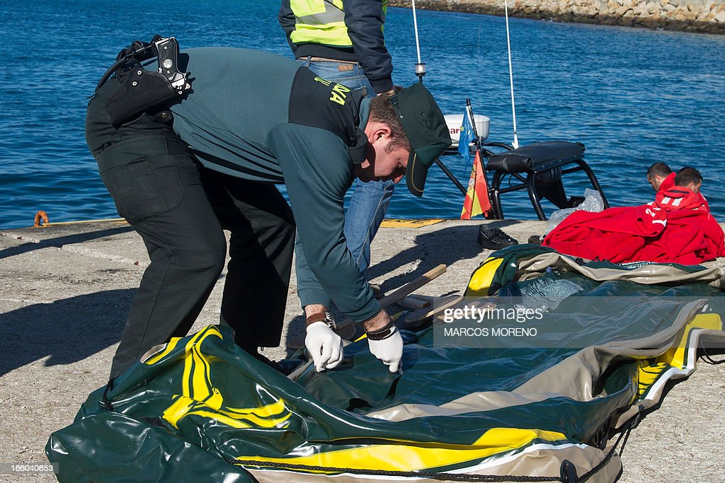A Guardia Civil policeman cuts an inflatable boat to avoid would-be immigrants to use it again at Tarifa's harbour, on April 8, 2013. Four inflatable boats carrying 31 sub-Saharan would-be immigrants across the Strait of Gibraltar were rescued today off the Spanish coast by the Spanish emergency services.