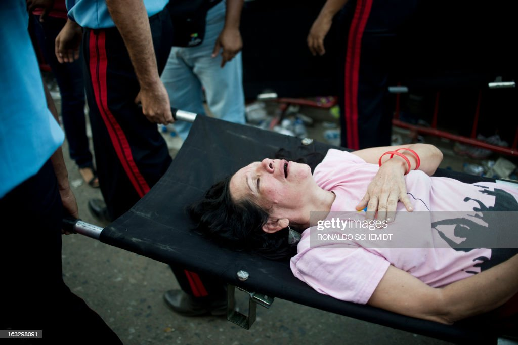 Guards carry a supporter as she fainted while waiting to pay respects to late Venezuelan President Hugo Chavez, outside the Military Academy in Caracas on March 7, 2013. Venezuelans filed past the open casket of late President Hugo Chavez as he lay in state after throngs of weeping loyalists gave the firebrand leftist a rousing farewell on the streets on the eve. AFP PHOTO/Ronaldo Schemidt